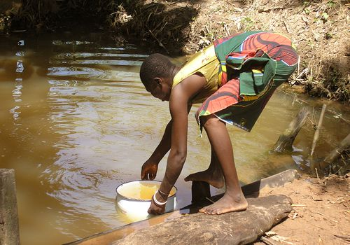 Person filling a pot with water from a river