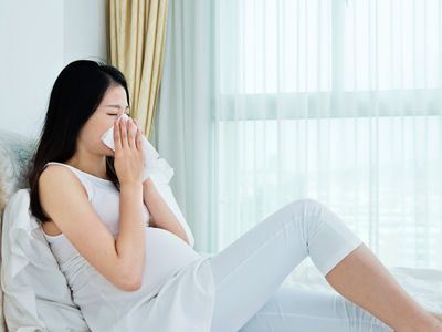 Pregnant woman blowing her nose in bed