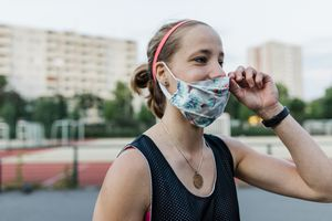 Woman exercising wearing a face mask.