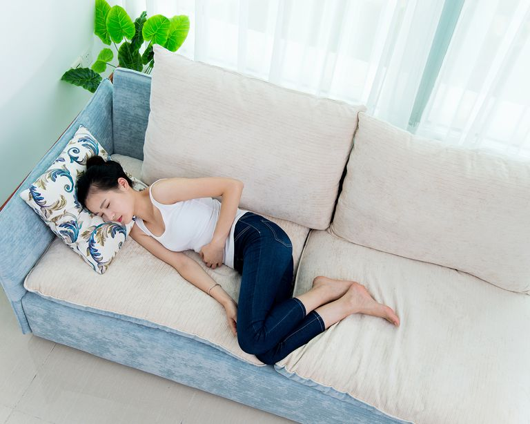 Young woman having stomachache on sofa.