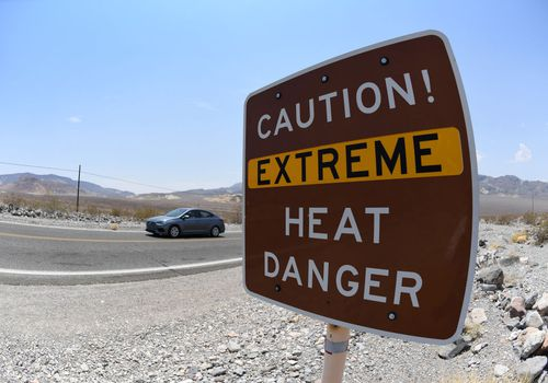 A warning sign posted alerts visitors of heat dangers in Death Valley National Park, California.