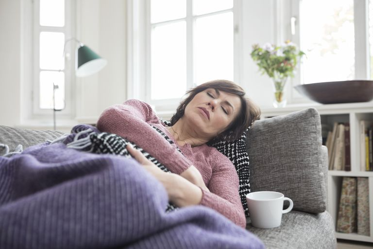 Woman with stomach ache lying on the sofa