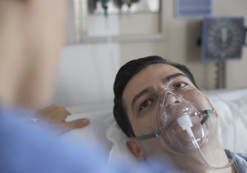 Man wearing an oxygen mask in the hospital