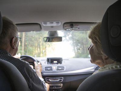 Senior couple driving in car