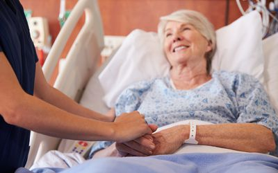 Close Up Of Hospital Nurse Holding Senior Patient's Hand