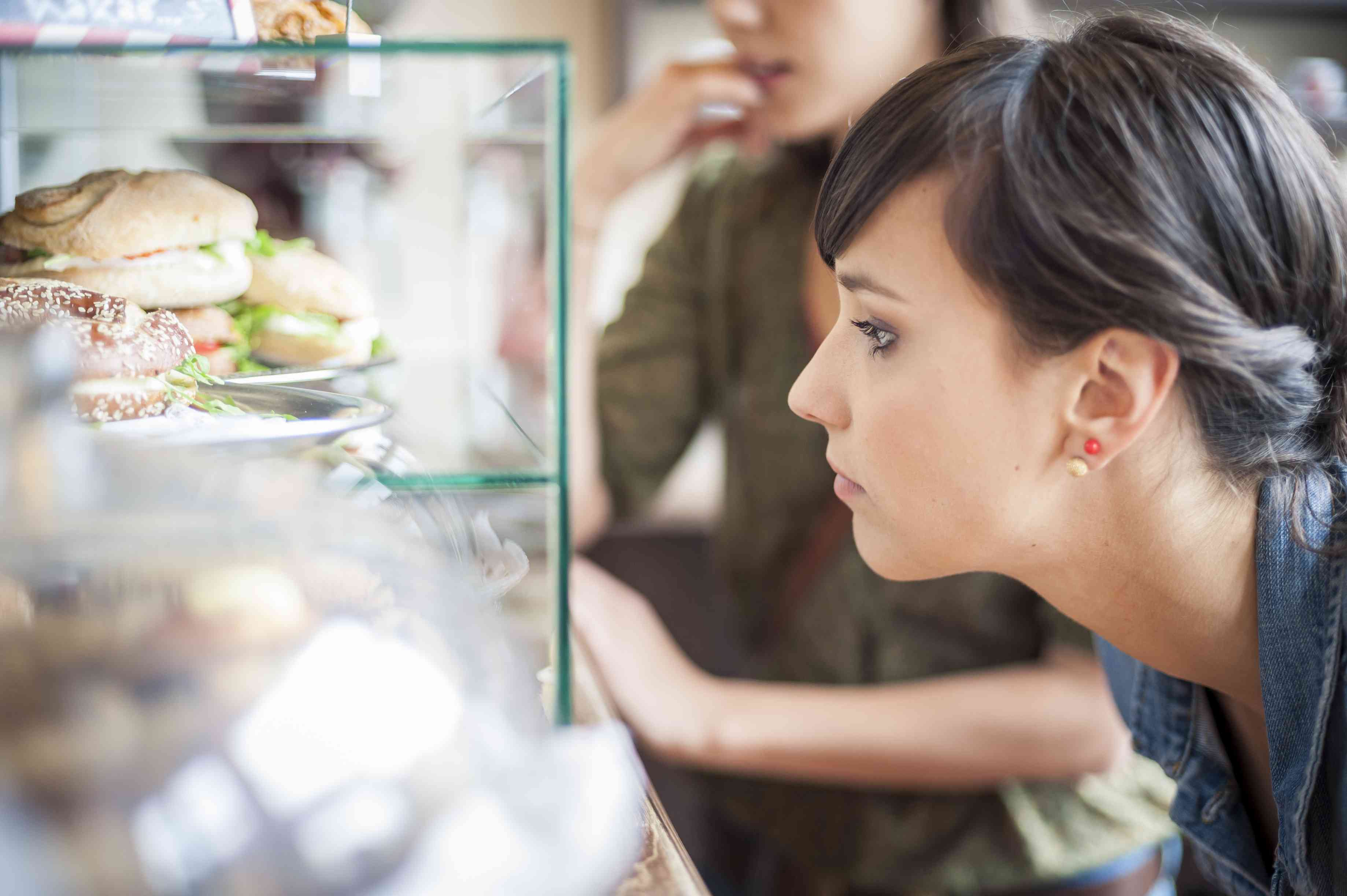 Woman looking at food in deli case