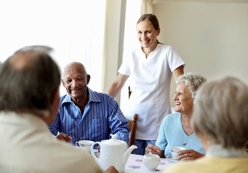 Nurse talking with seniors in an assisted living facility