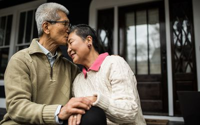 Senior couple embracing in front of home