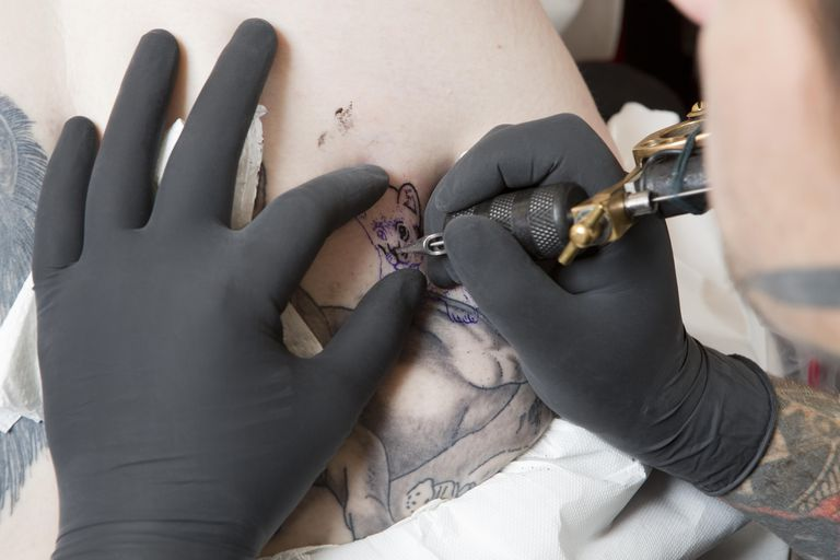 A tattoo artist doing a tattoo on someones back
