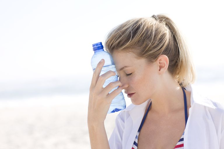 Young woman holding water bottle against forehead