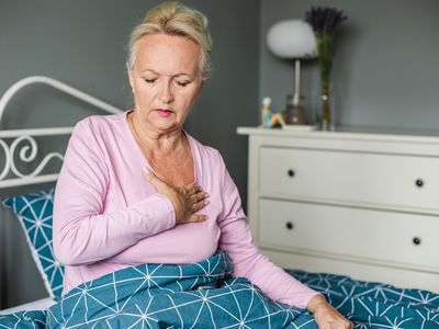 Senior woman suffering from chest pain in bed