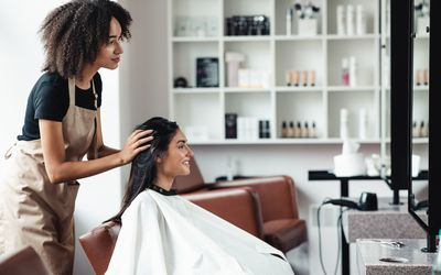 Young woman looking for changes, trying new hairstyle at beauty salon - stock photo