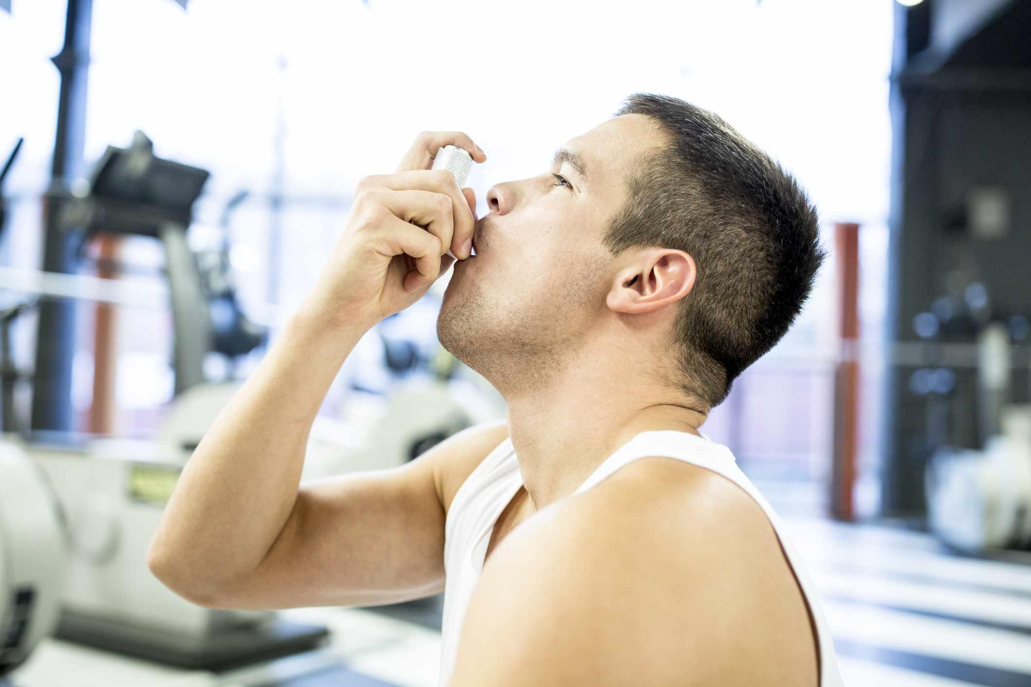 Young man using inhaler at gym