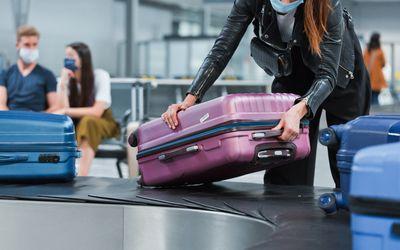 Traveler wearing face mask getting their luggage.
