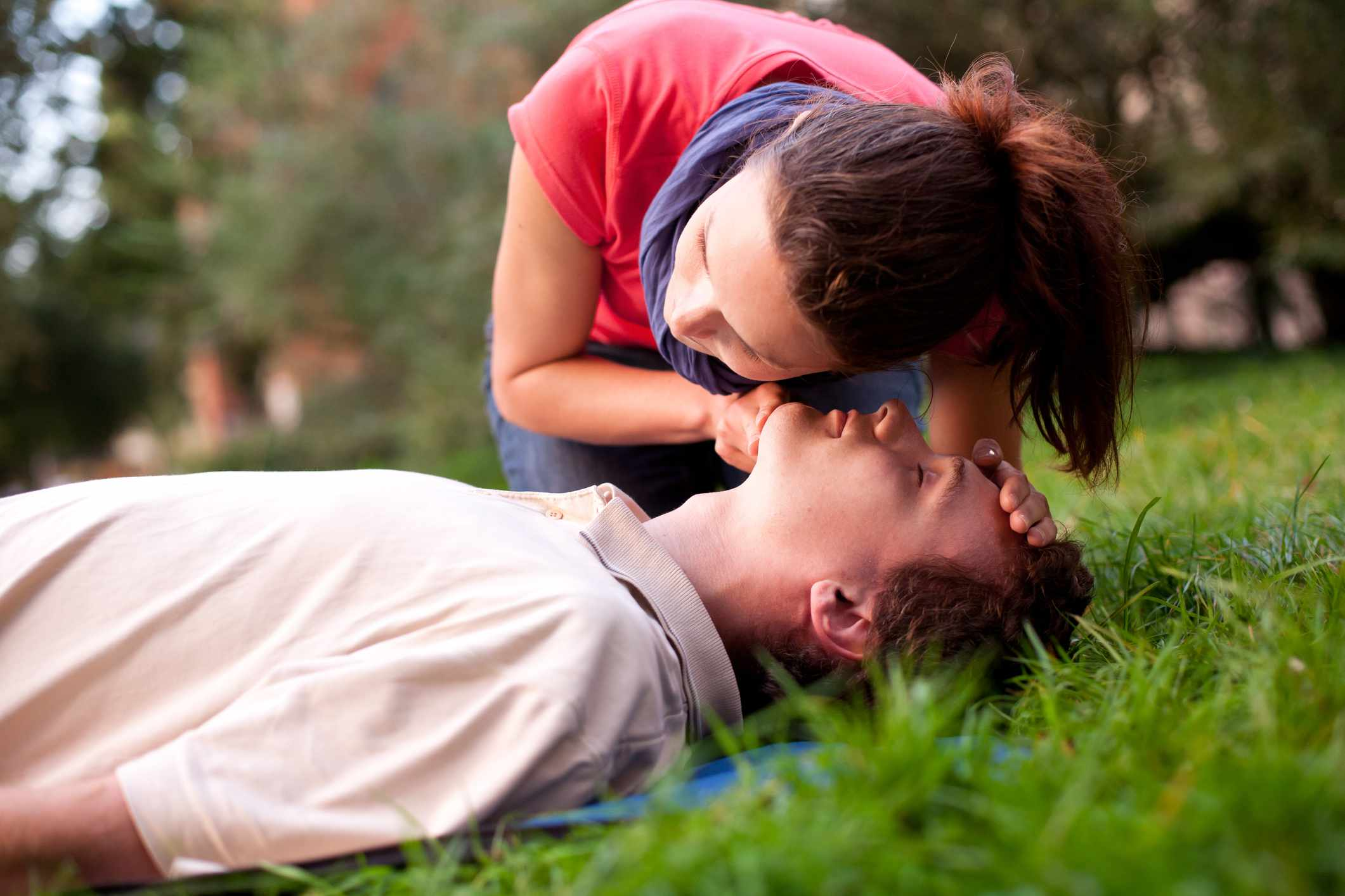 A woman applying CPR on a man