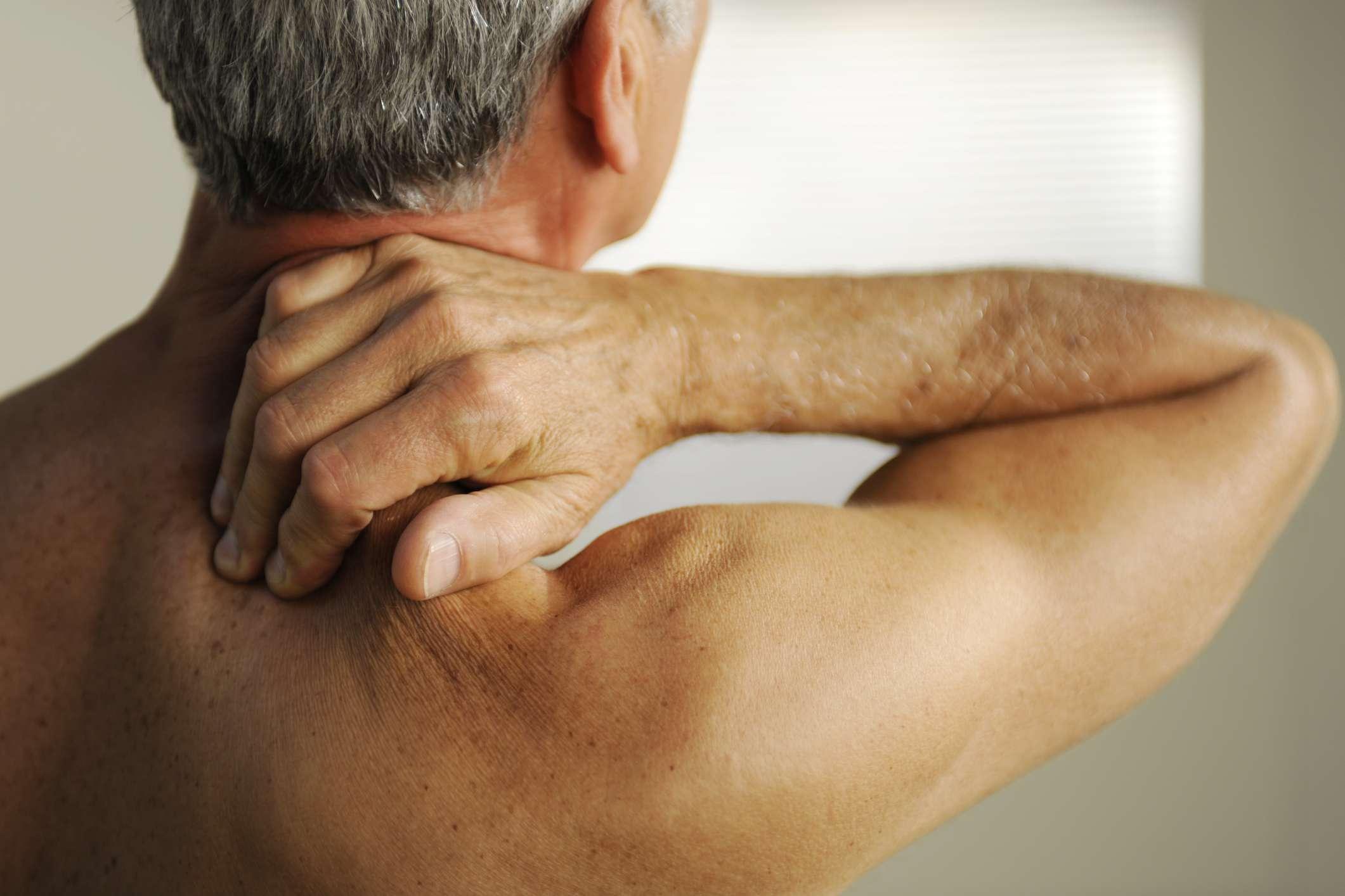 Shirtless man rubbing his neck in pain