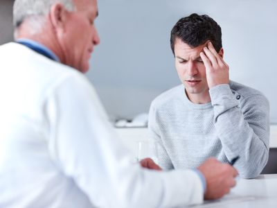 Man in pain getting prescription from doctor