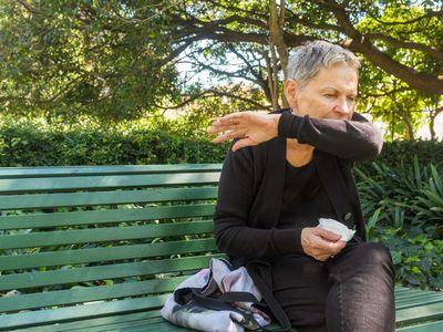 Older woman sitting on park bench coughing into elbow and holding a tissue