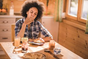 a woman covering her mouth at breakfast