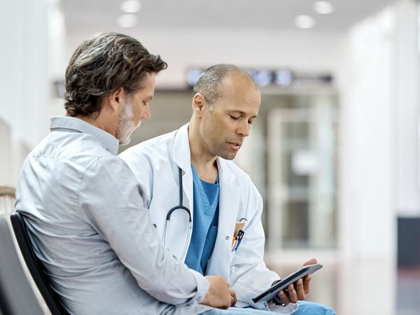 Doctor reviewing information on tablet with male patient