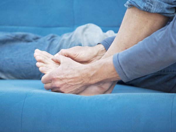 person with gout holding foot