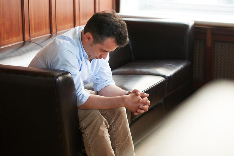 Man sitting on couch clasping his hands together