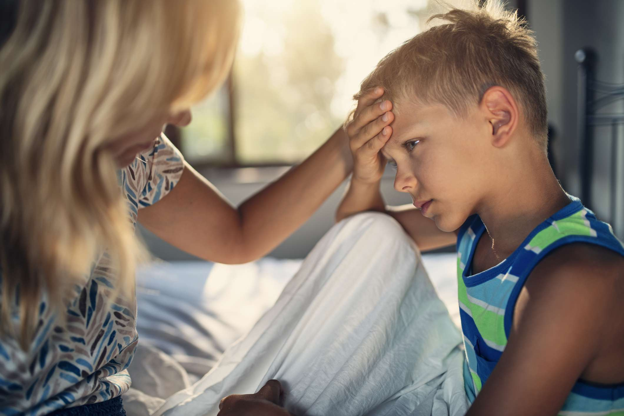 A white male child in bed holding his head; his blonde female caregiver is comforting him.
