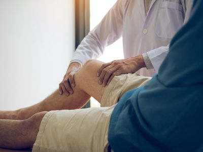 physical therapist checking a patient's knee for pain