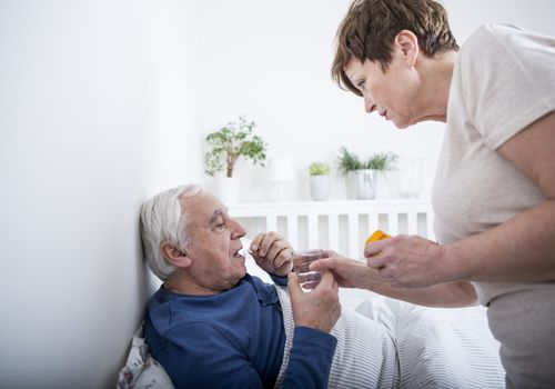 A woman helping an older man take his medication in bed