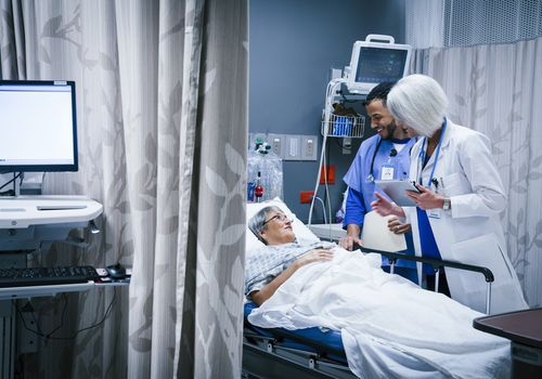 Doctor and nurse talking with patient in hospital bed