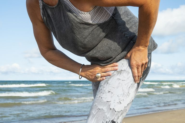 A woman with hip pain at the beach