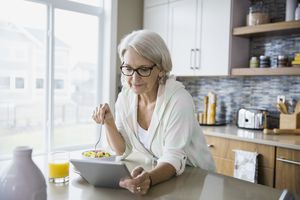 Woman standing in the kitchen eating fruit salad and looking at a digital tablet