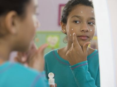 Girl applying acne medication in mirror