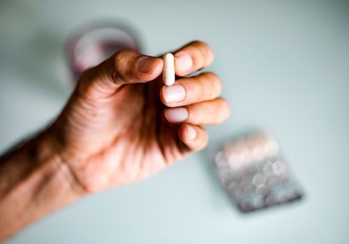 A man's hand holding a capsule / pill - stock photo