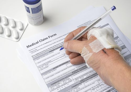 Photo of a person with an injured hand filling out a medical claim form