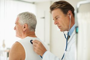 Doctor listening to man's breathing in doctor's office