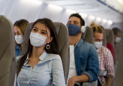 People on an airplane wearing face masks.