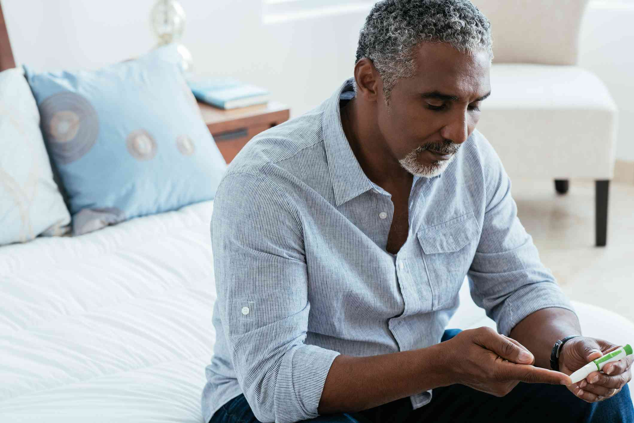 Mature man checking diabetes in bedroom - stock photo
