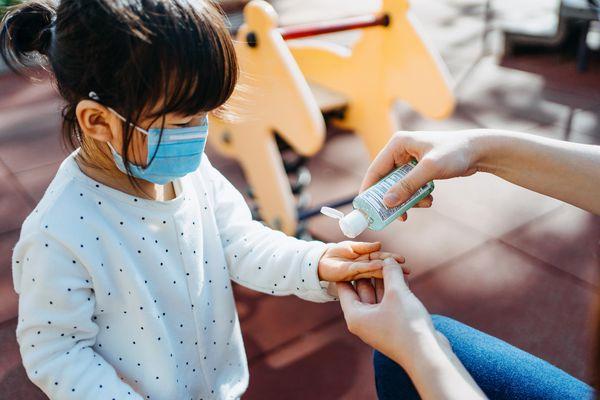 parents applies hand sanitizer to child