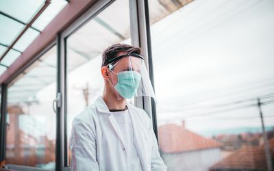 male healthcare worker wearing mask and face shield