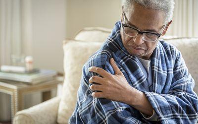 Senior man rubbing his shoulder