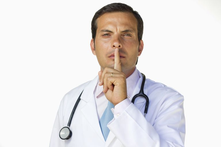 "Male physician with his finger across his lips saying ""Shhh."""