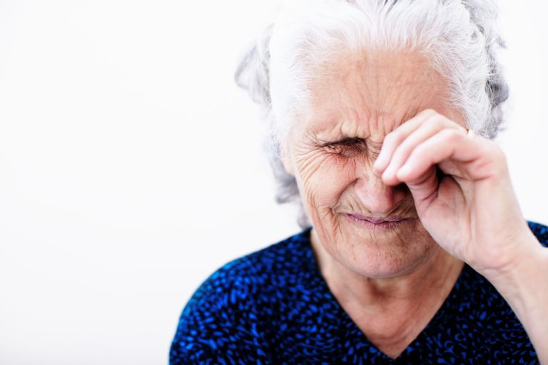 elderly woman rubbing her eye