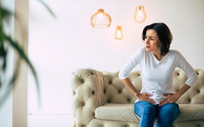 A woman is sitting on the couch holding her lower abdomen with a look of pain on her face.