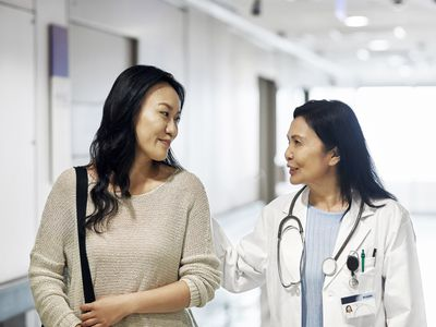 Smiling mature doctor talking to woman in hospital