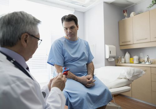 Doctor explaining heart model to patient in examination room