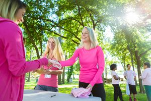 Women happily signing up at breast cancer awareness event