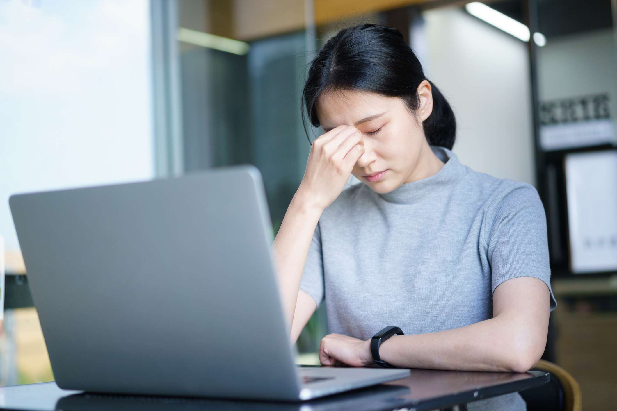 a woman tired from looking at her laptop