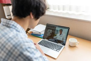 Asian man video chatting with doctor at home