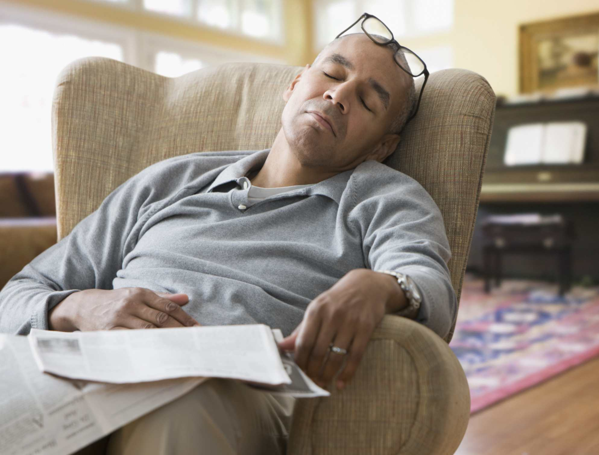 A man dozes off while reading the newspaper